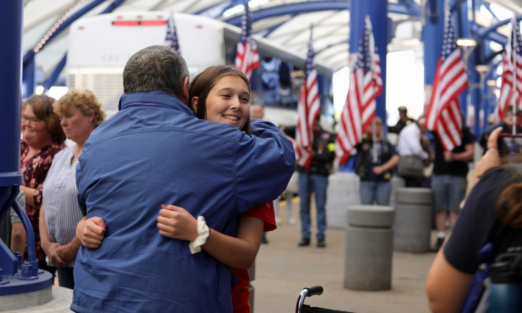 Ella Sickles, a high school student from Midlakes, is shown hugging a fellow participant on the Soaring Valor trip.