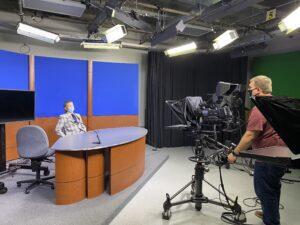 Cameraman filming FLCC student behind desk in TV studio