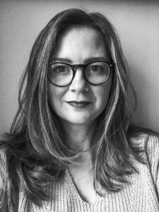 black and white headshot of a woman with long hair and glasses