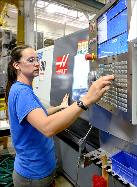 Woman operating computerized machinery